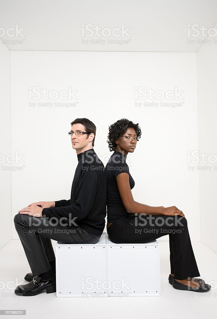 Man and woman in a white room look toward camera stock photo