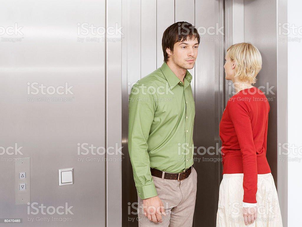 Um homem e mulher em um elevador foto de stock royalty-free