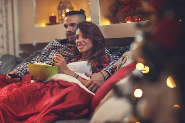 mann und frau im bett vor dem fernseher und essen popcorn - mädchen night snacks stock-fotos und bilder