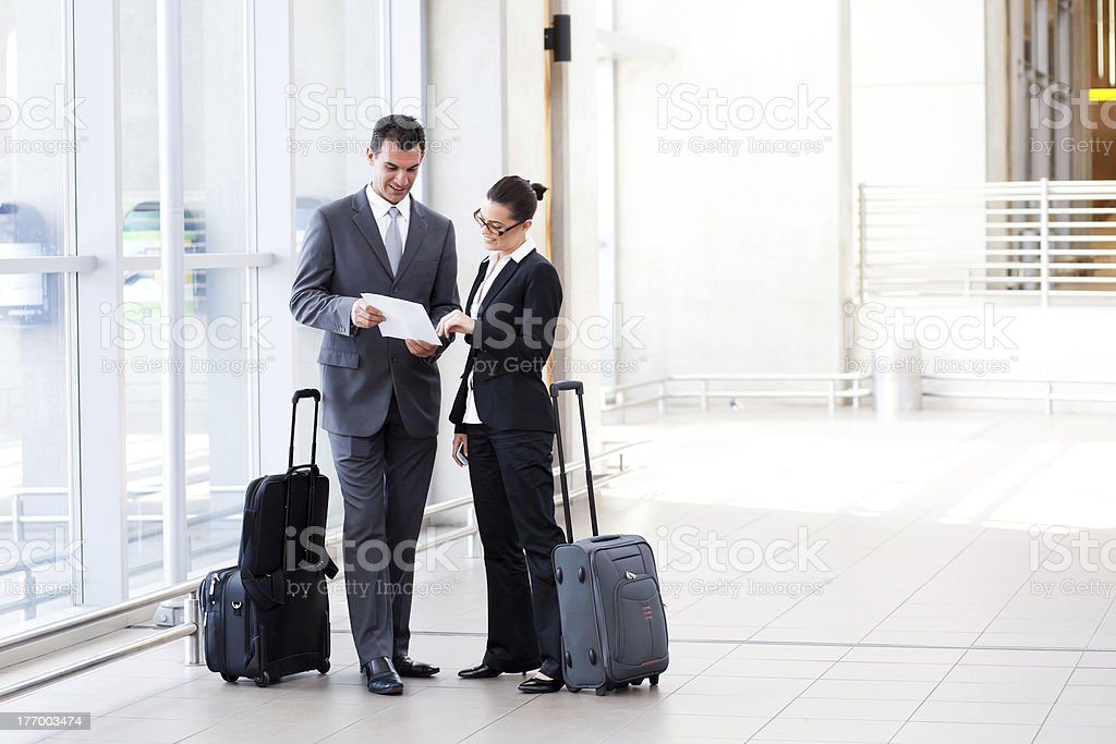 Man and woman in business attire with luggage stock photo