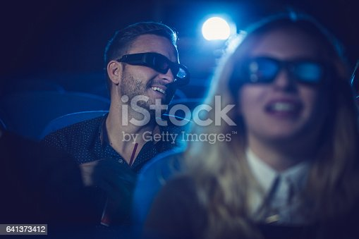 Group of people, watching a movie in cinema, they are smiling.
