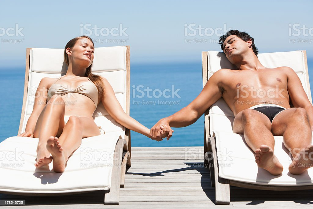 Man and woman in deck chairs sunbathing, holding hands stock photo