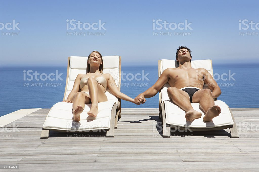 Man and woman in deck chairs sunbathing holding hands royalty-free stock photo