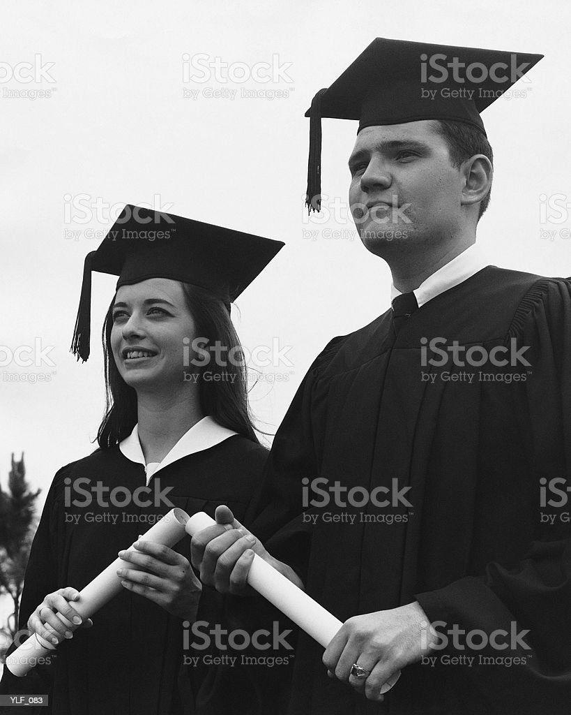 Man and woman in graduation caps and gowns royalty-free stock photo