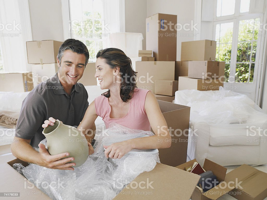 Man and woman in house with boxes unpacking vase royalty-free stock photo