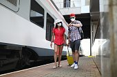 Man and woman in medical protective masks walk along the train with suitcase. Security at airports and train stations in pandemic concept