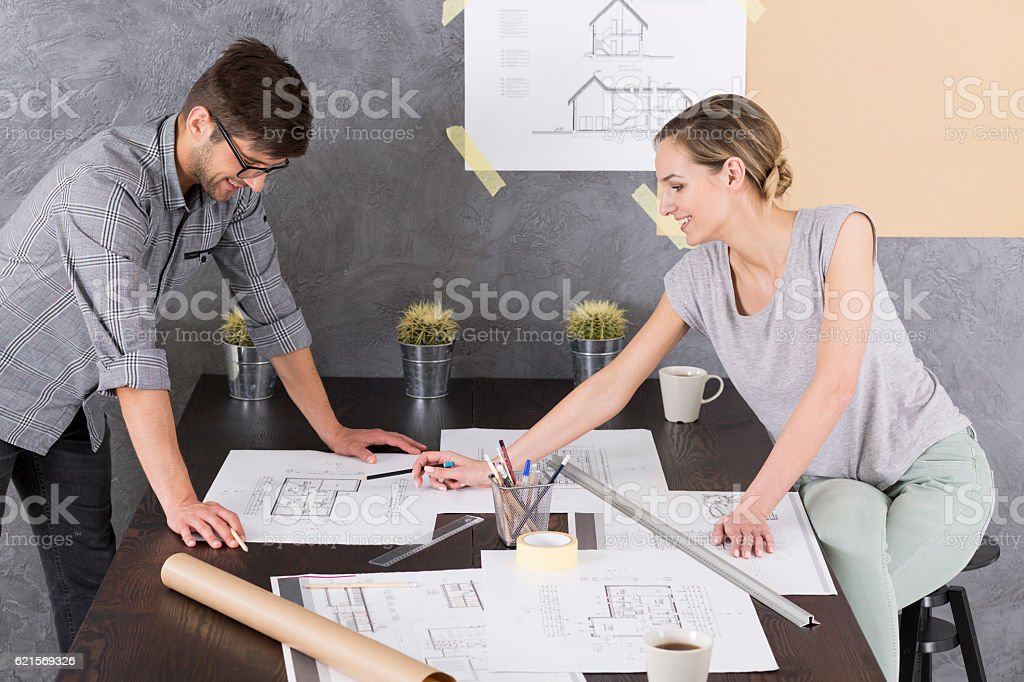 Man and woman in office with documents and drawings photo libre de droits