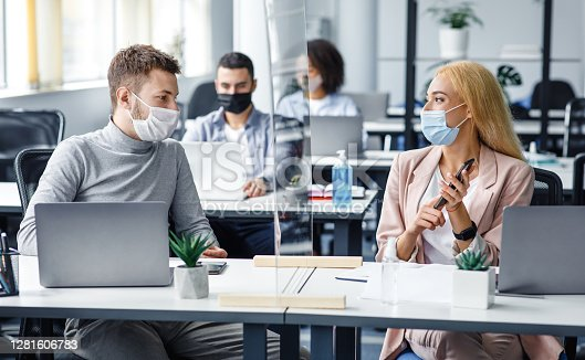 Man and woman in protective masks maintain social distance at work. Employees discuss work sitting at table laptop with antiseptic, smartphone and protective glass in office interior, panorama