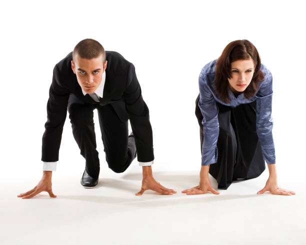 Man and woman in racers ready position on the ground stock photo