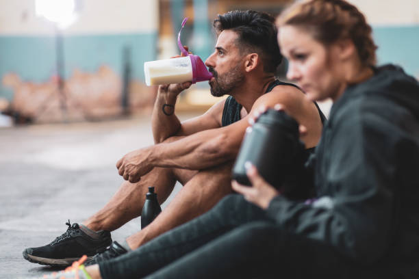 man and woman in sports clothing drinking protein drinks - protein stock photos and pictures