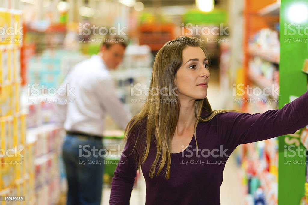 Man and woman in supermarket with shopping cart royalty-free stock photo