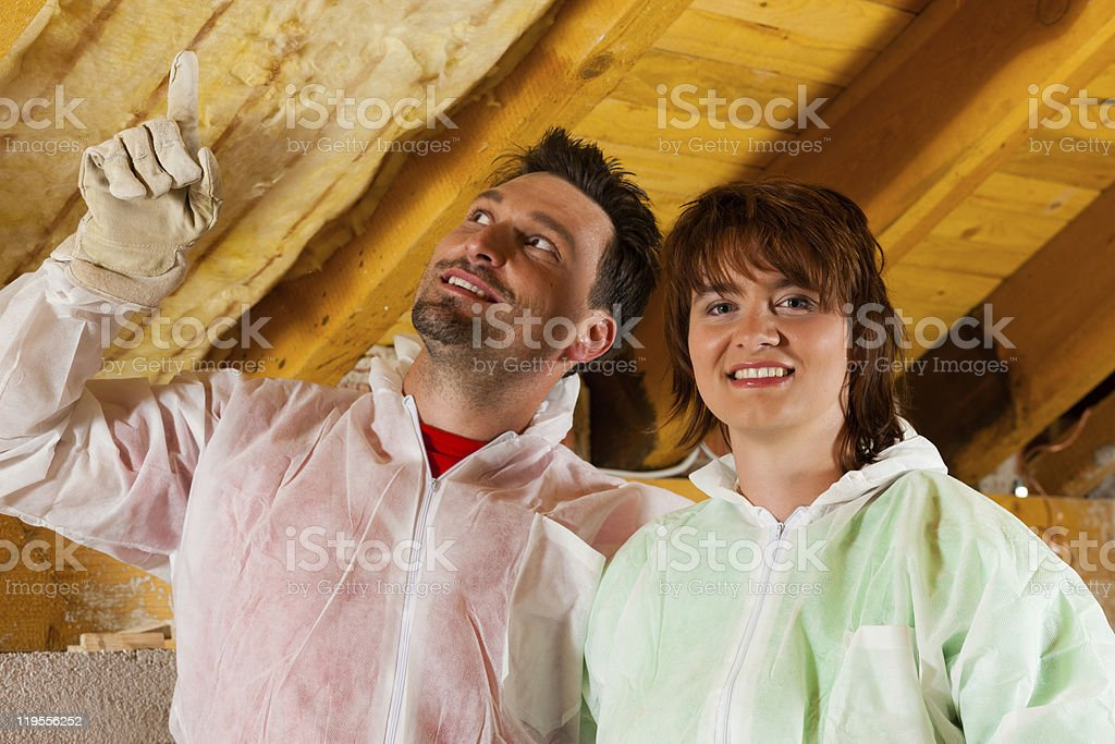 A man and woman in white coveralls in partly insulated room  stock photo