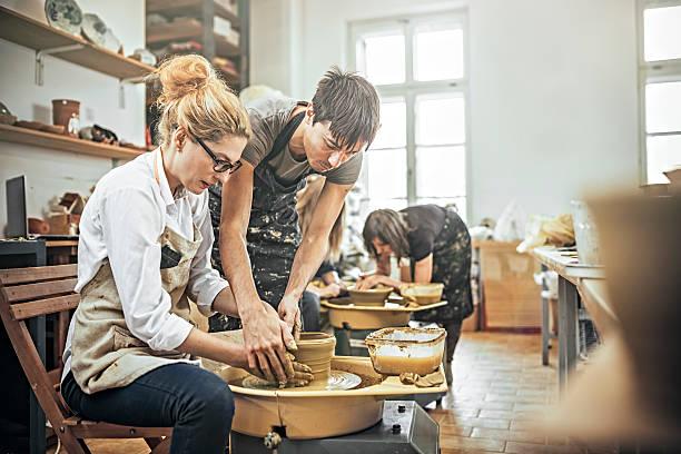 man and woman in workshop working on pottery wheel - alfarería fotografías e imágenes de stock