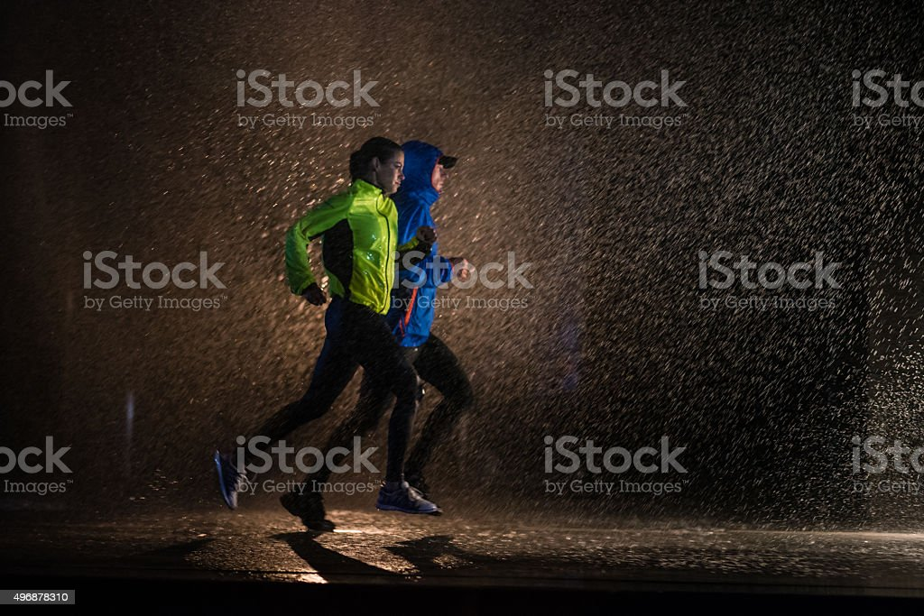 Man and woman jogging in city stock photo