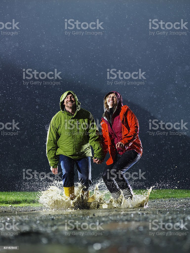 Man and woman jumping in a rain puddle. royalty free stockfoto