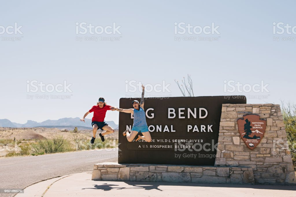 Man and Woman Jumping In Front of Park Sign stock photo
