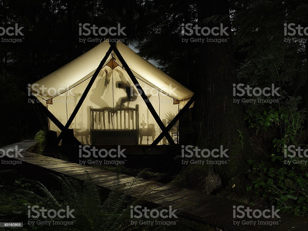 Man and woman jumping on bed inside tent. royaltyfri bildbanksbilder
