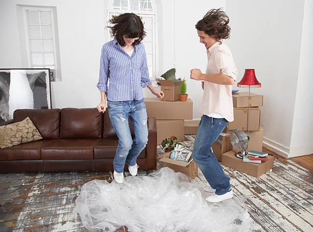 Man and woman jumping on bubble wrap in home with cardboard boxes stock photo