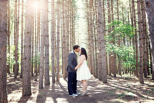 mann und frau küssen im wald - bräutigam jeans stock-fotos und bilder
