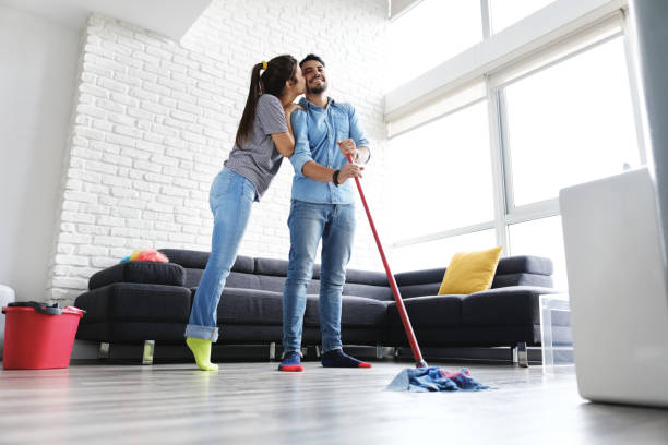 Man And Woman Kissing While Cleaning Home stock photo