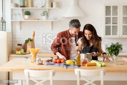 Happy man and woman preparing dinner or lunch from fresh health ingredient. Husband hugging smiling wife. Couple rejoice at resulting delicious dish. Laughing family domestic portrait. Cook on kitchen