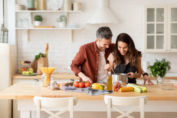 Man and woman laughing cook dinner on kitchen stock photo