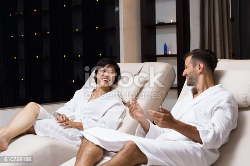 610769340istockphoto Man and Woman Laughing on Loungers in Spa Salon 610769186
