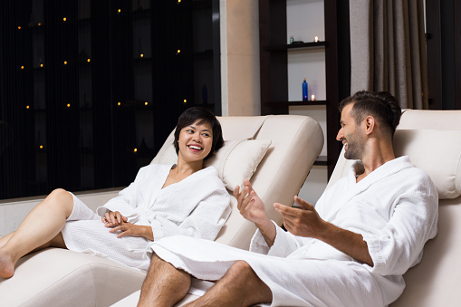 610769340 istock photo Man and Woman Laughing on Loungers in Spa Salon 610769186