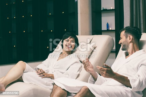610769340istockphoto Man and Woman Laughing on Loungers in Spa Salon 953553290