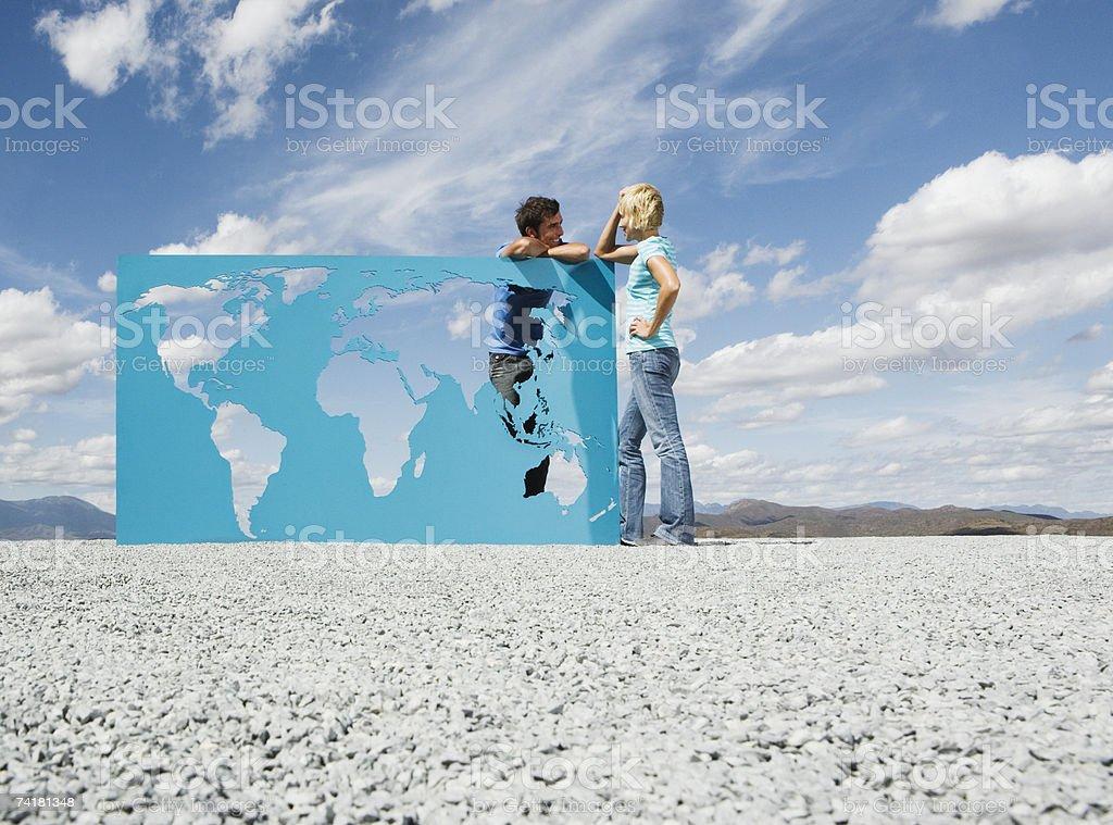Homem e mulher, Inclinar-se no mapa do mundo ao ar livre foto de stock royalty-free