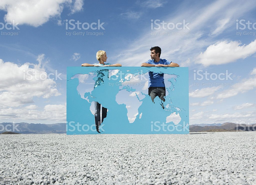 Man and woman leaning on world map outdoors royalty-free stock photo