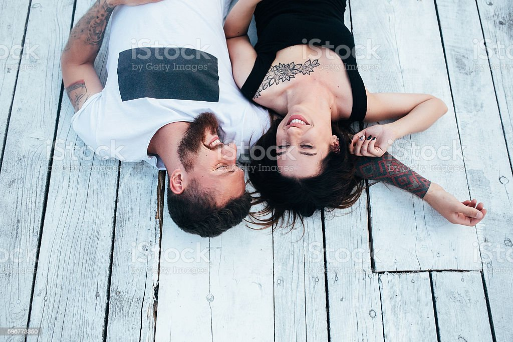 man and woman lie on the wooden floor stock photo