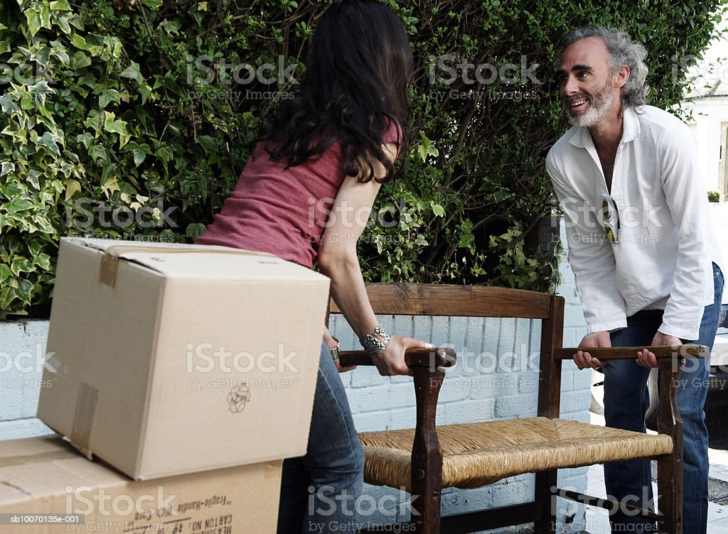 Man and woman lifting bench together in garden royalty-free stock photo