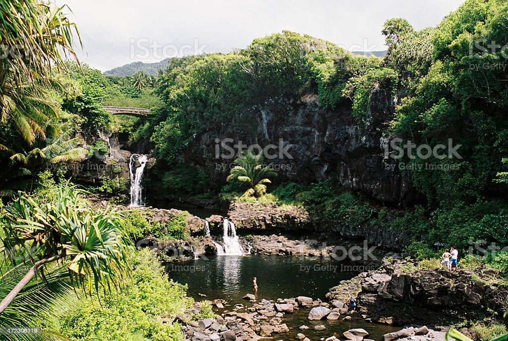 Man and woman look at Maui Hawaii waterfall royalty-free stock photo
