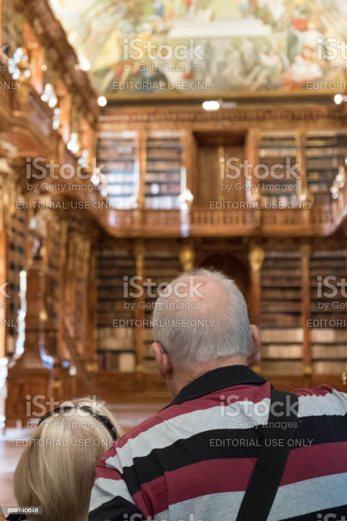 Man and woman look inside Philosophical Hall at the library of the Strahov Monastery. 17th Century library within the monastery in Prague. stock photo