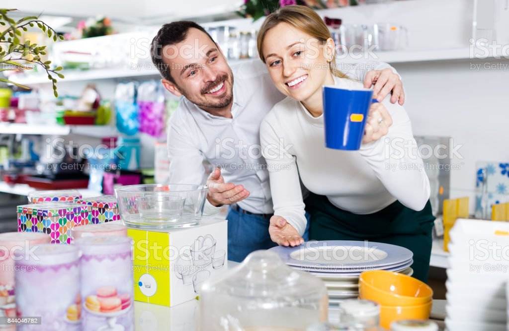 Man and woman looking at a blue cup stock photo