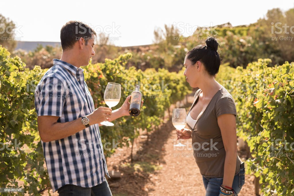 A man and woman looking at a bottle of wine stock photo