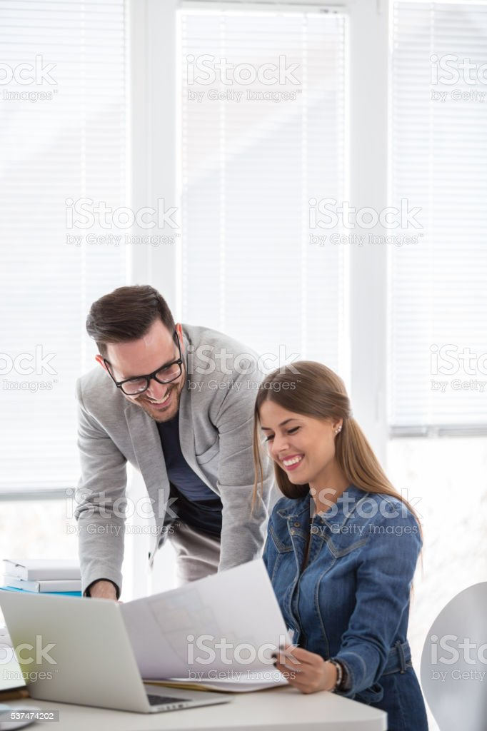 Man and woman looking at documents in the office stock photo