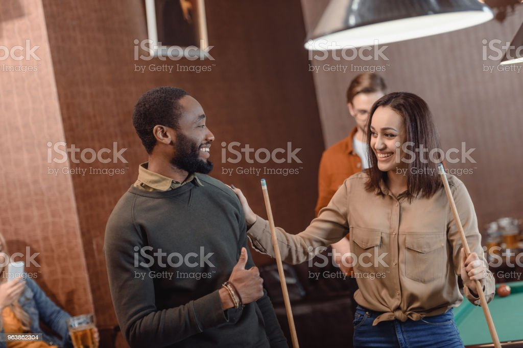 man and woman looking at each other in pool bar with friends - Royalty-free Adult Stock Photo