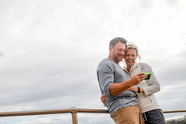 man and woman looking at smartphone - 40 49 years stock pictures, royalty-free photos & images