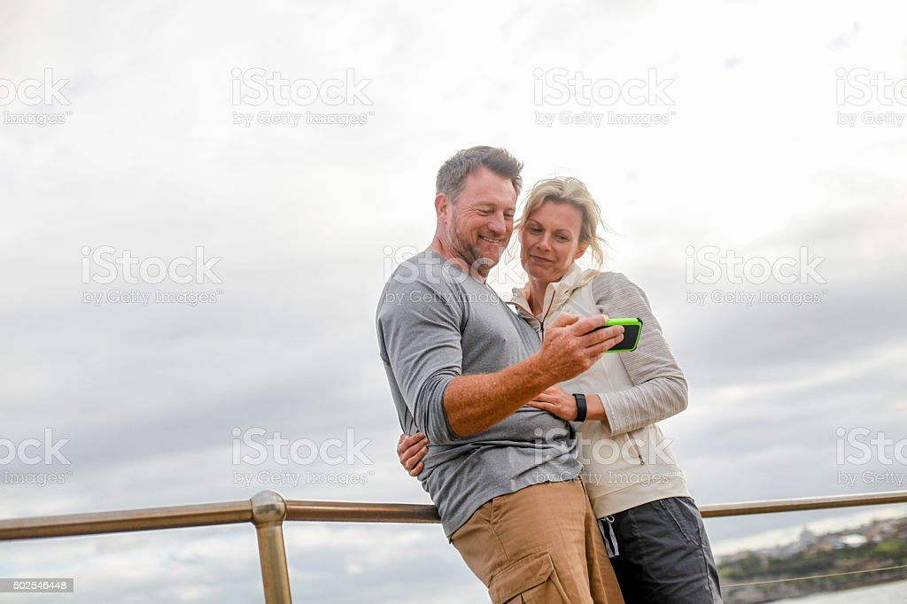 Man and Woman looking at smartphone stock photo