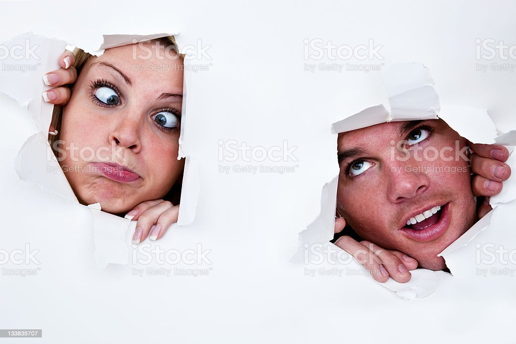 Man and woman looking through holes in paper royalty-free stock photo