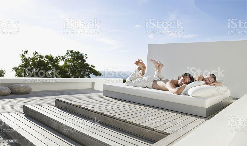 Homme et femme allongée sur le lit en plein air avec Zone Bleue - Photo
