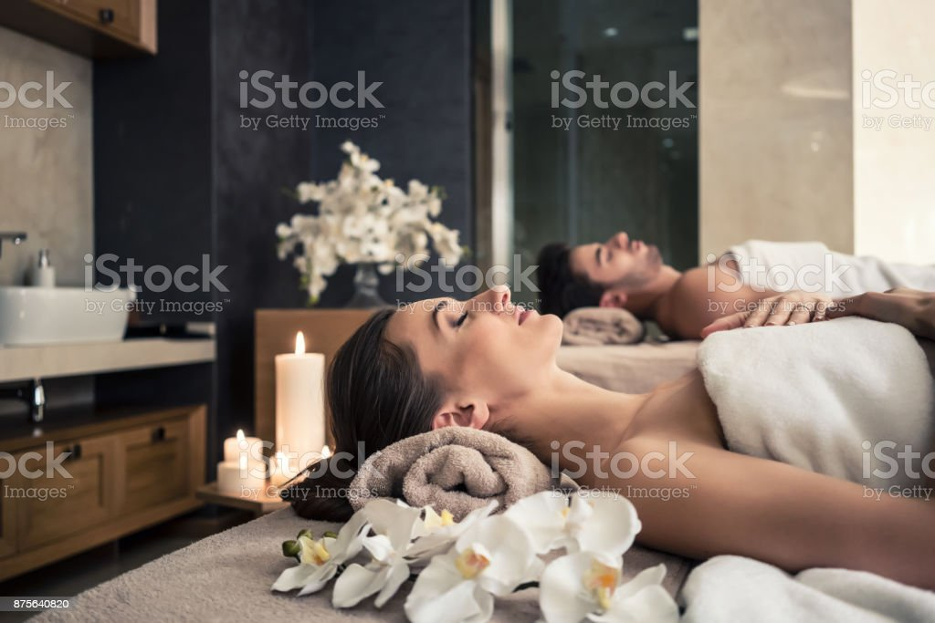 Man and woman lying down on massage beds at Asian wellness center stock photo