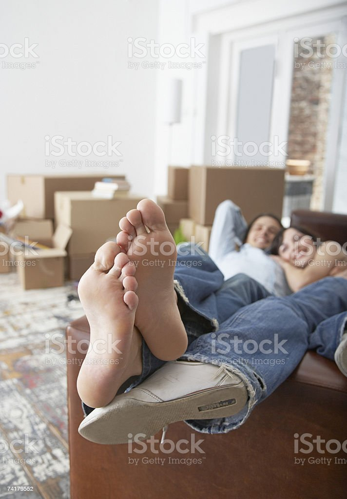 Man and woman lying down on sofa in home with cardboard boxes stock photo