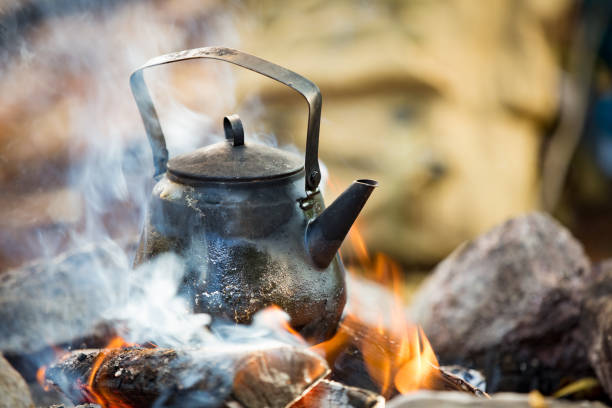 Man and woman making coffee in big kettle on campfire stock photo