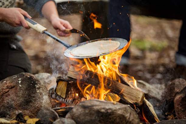 Man and woman making pancakes on campfire stock photo