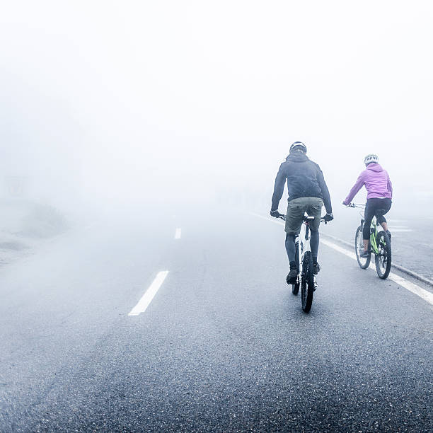 Man and Woman Mountain Biking in Fog stock photo