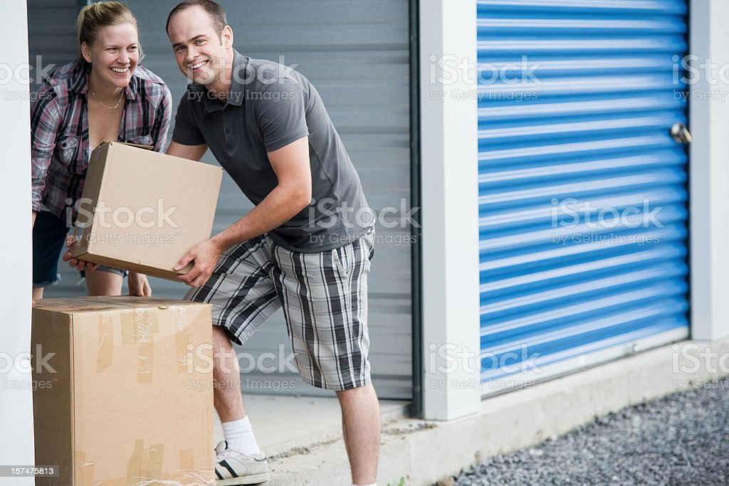 Man and Woman Moving Boxes at Self Storage Unit stock photo