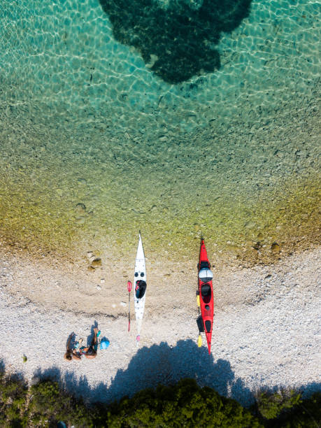 Man and woman on a beach with kayaks stock photo